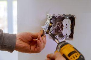 man fixing a light switch